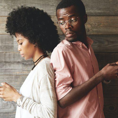 homme et femme dos à dos sur leur téléphones
