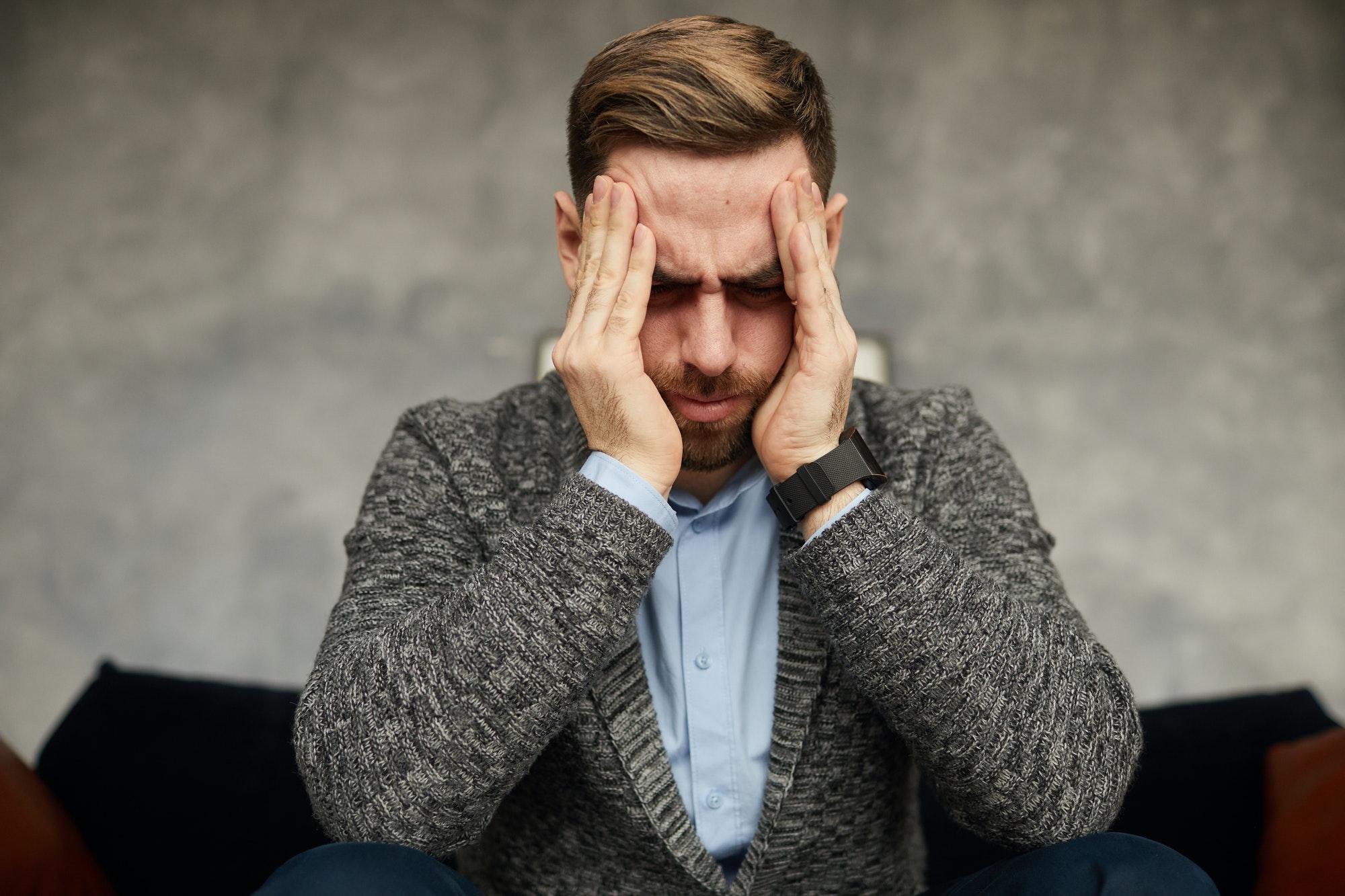 homme se tient la tête fatigué du harcèlement de son ex