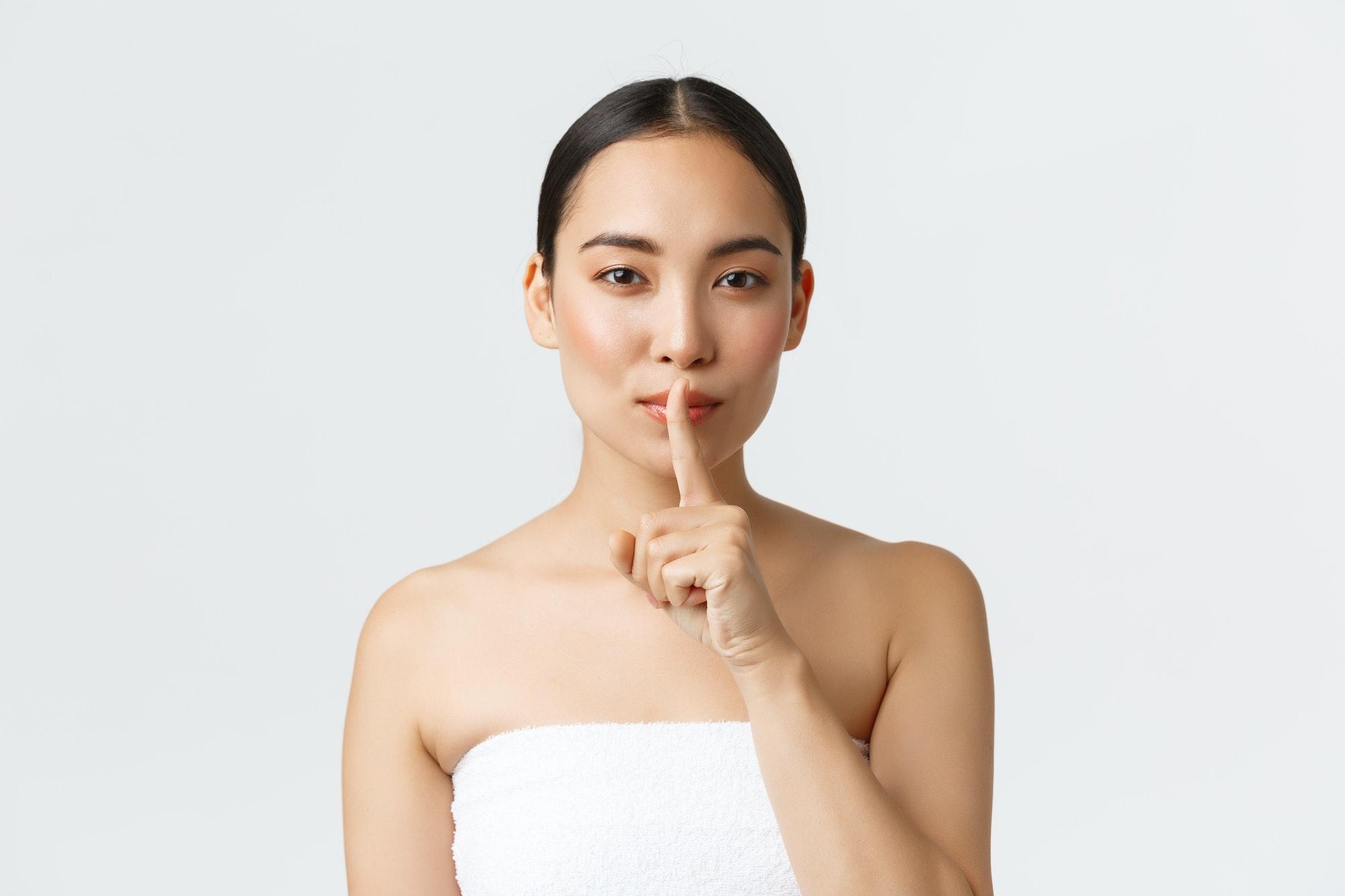 Femme met son doigt sur sa bouche. Elle ne dit pas tout