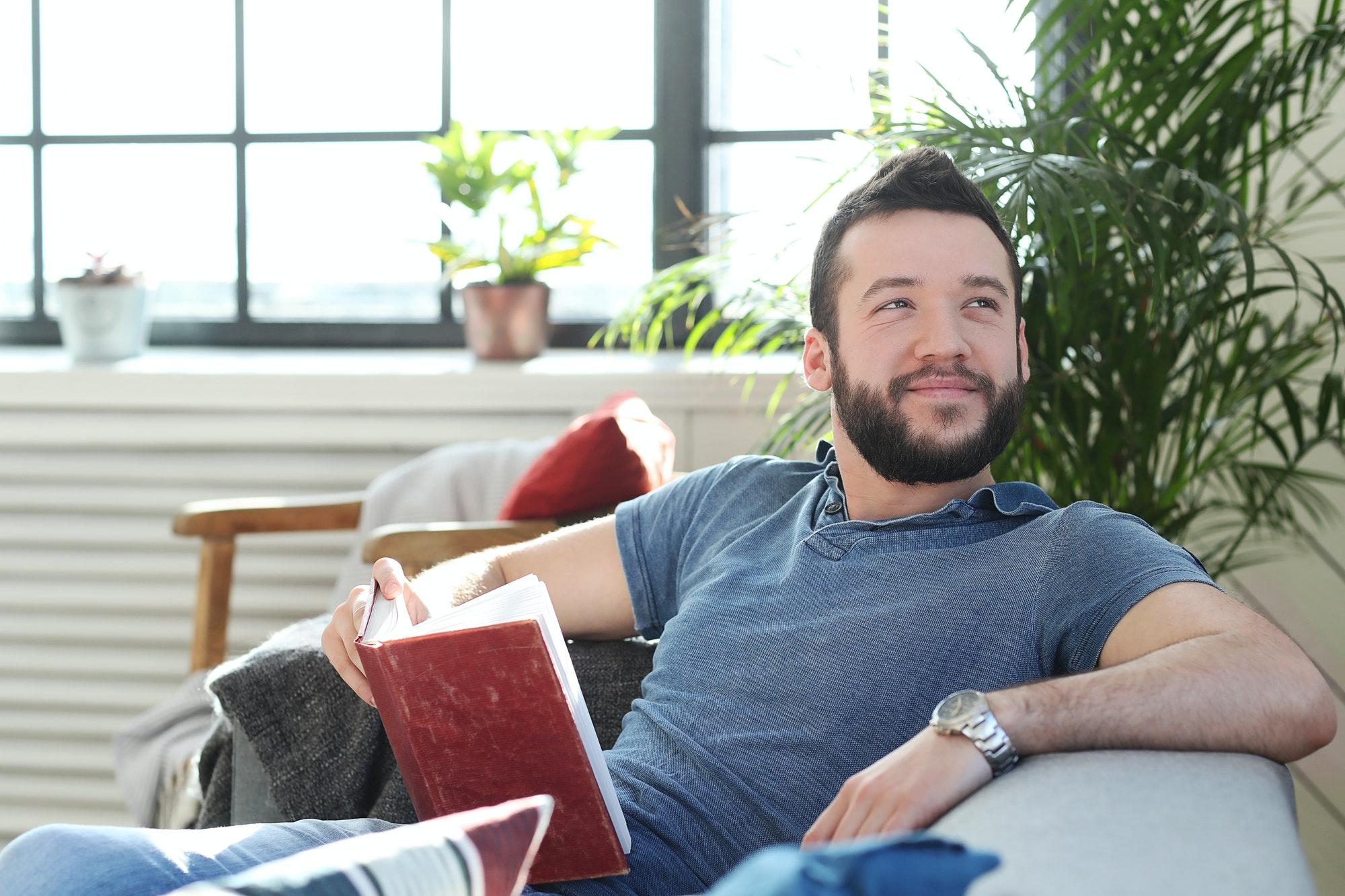 homme souriant lit un livre