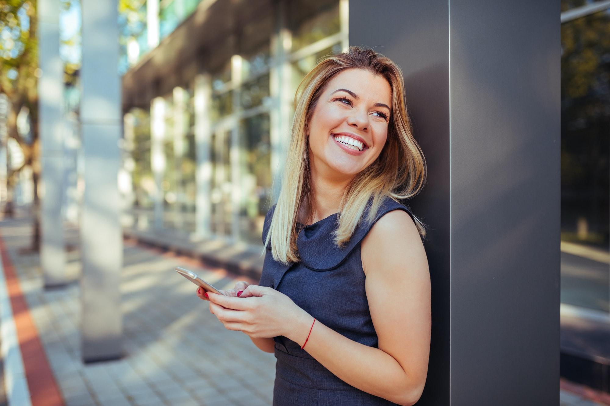 femme souriante tiens son téléphone dans ses mains