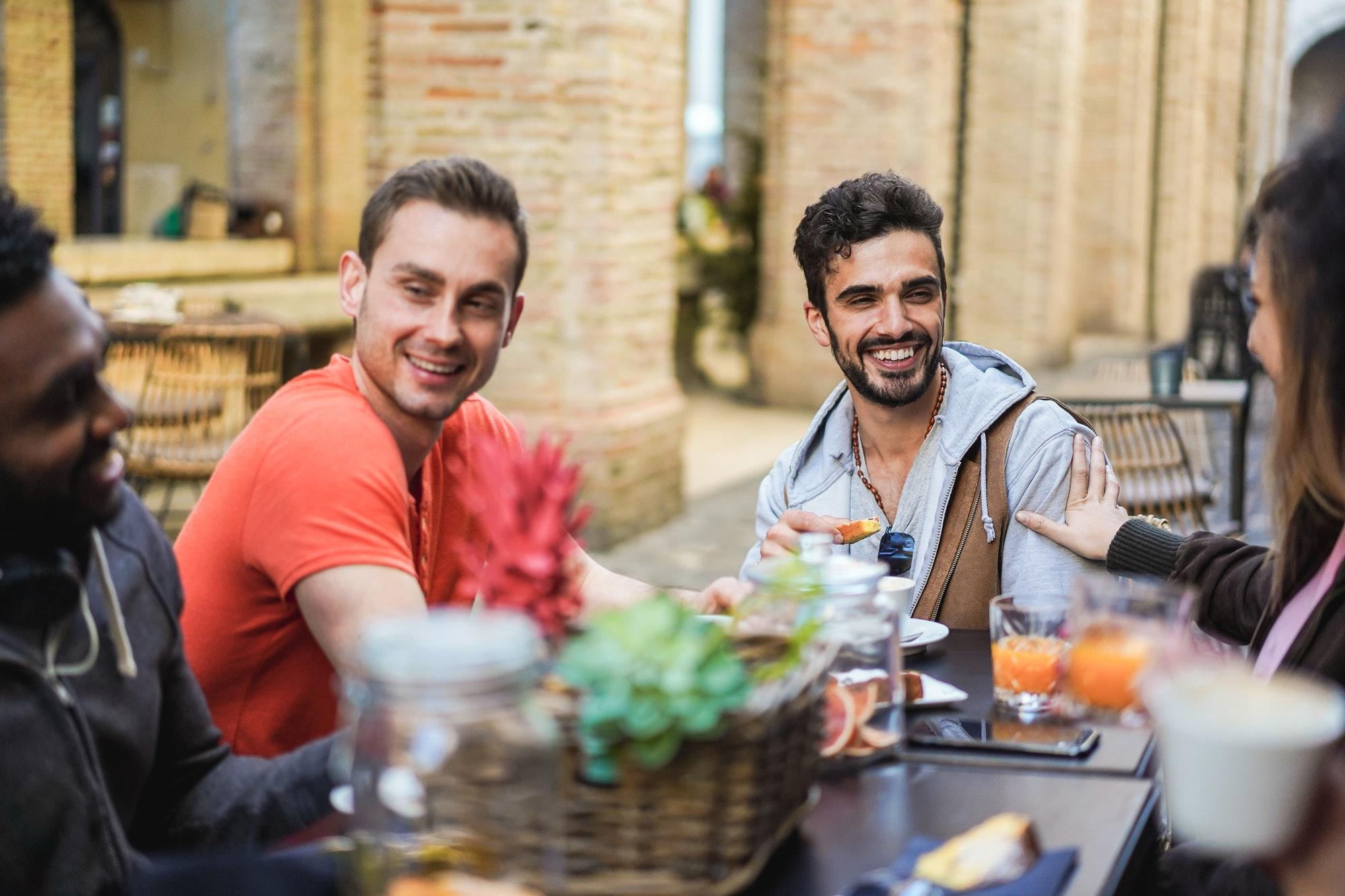 groupe de jeunes adultes rient autour d'une table