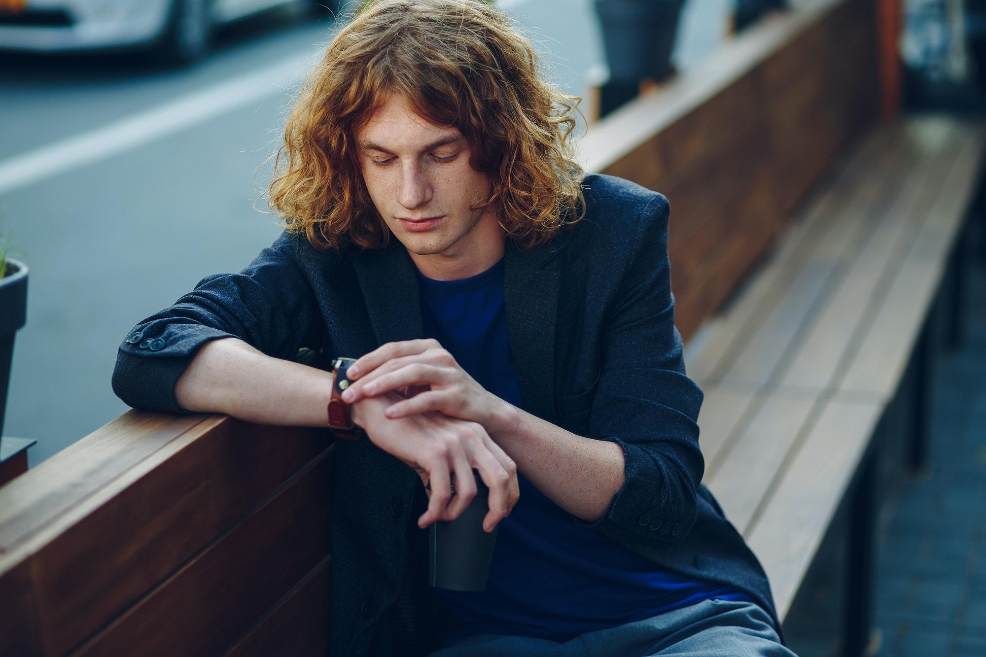 homme regarde sa montre assis sur un banc