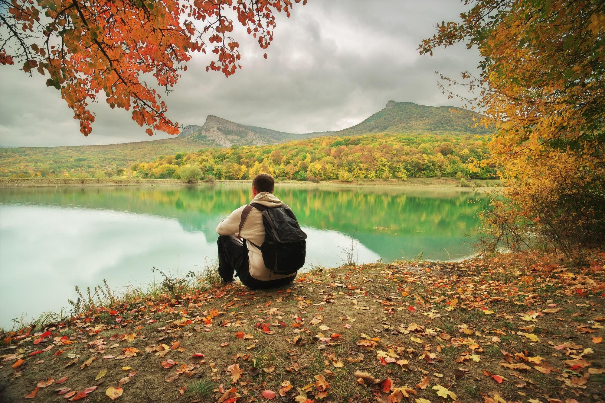 homme assis seul au bord d'un lac