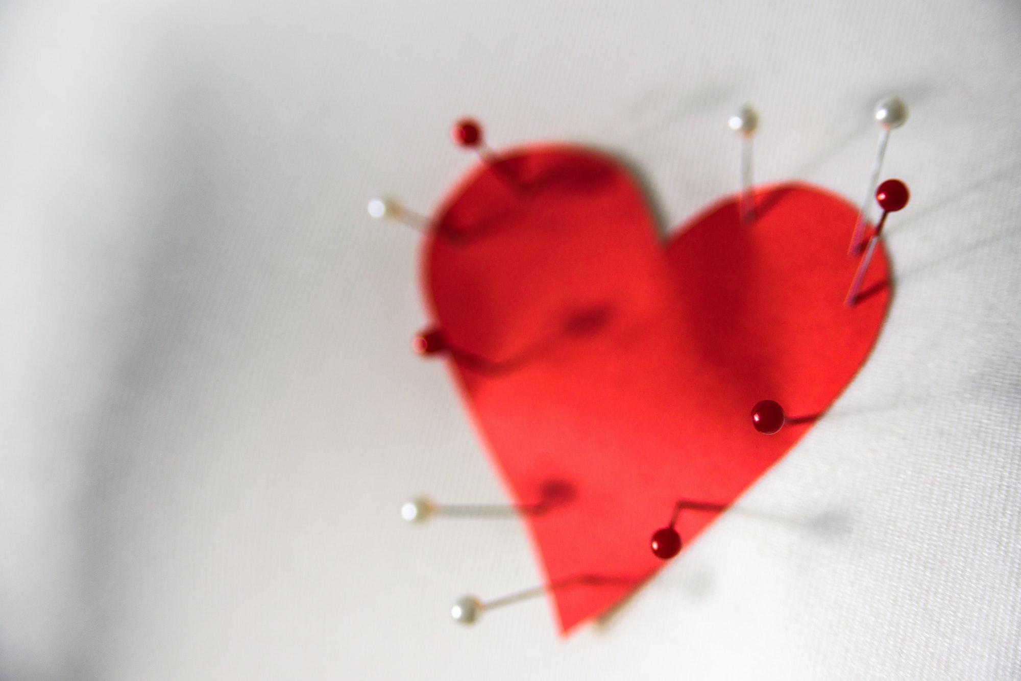 """coeur en papier percé d'épingles pour symboliser 'jouer avec les sentiments"""""""
