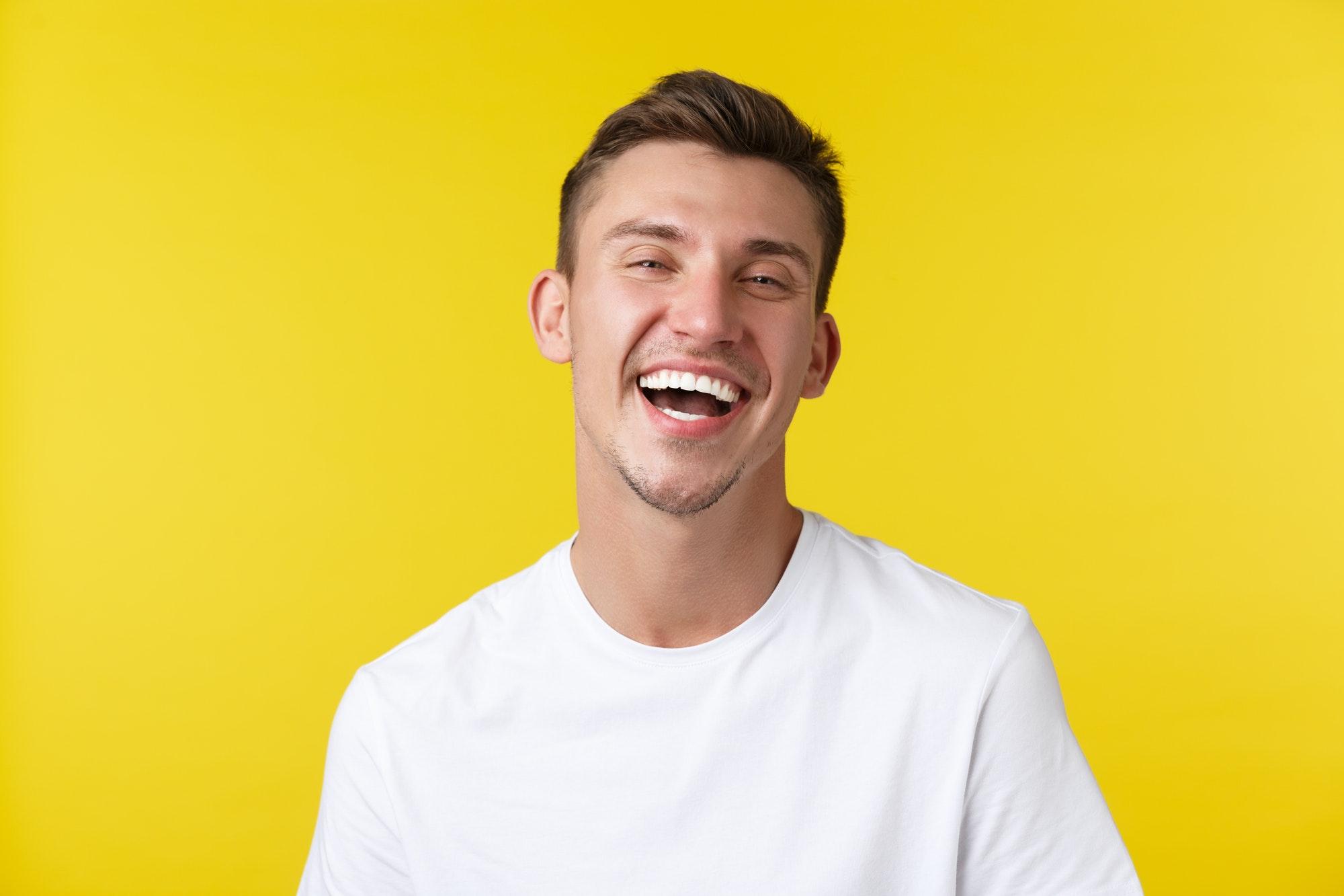 homme heureux et souriant sur fond jaune