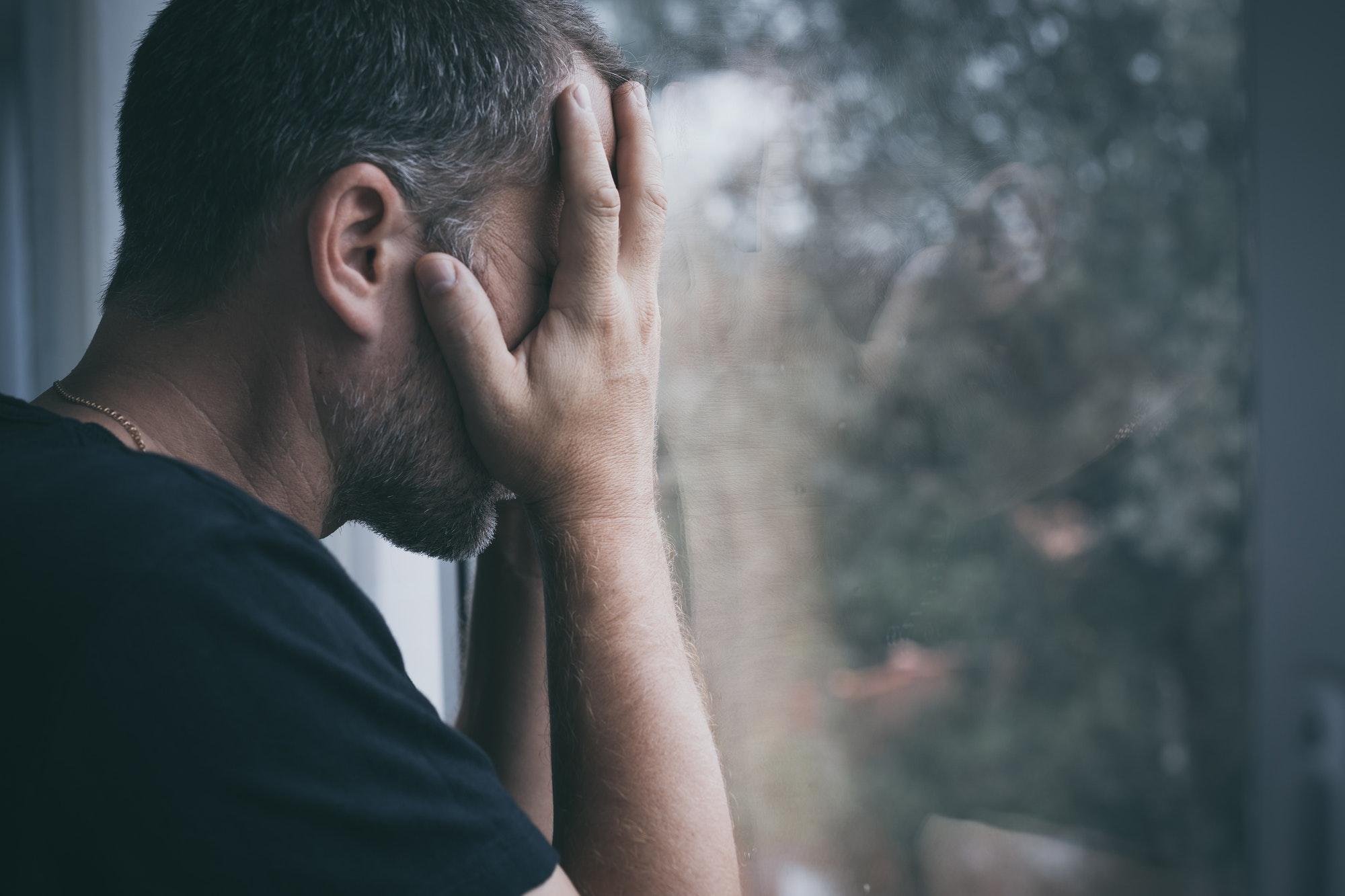 Homme devant sa fenêtre triste parce que son ex lui manque