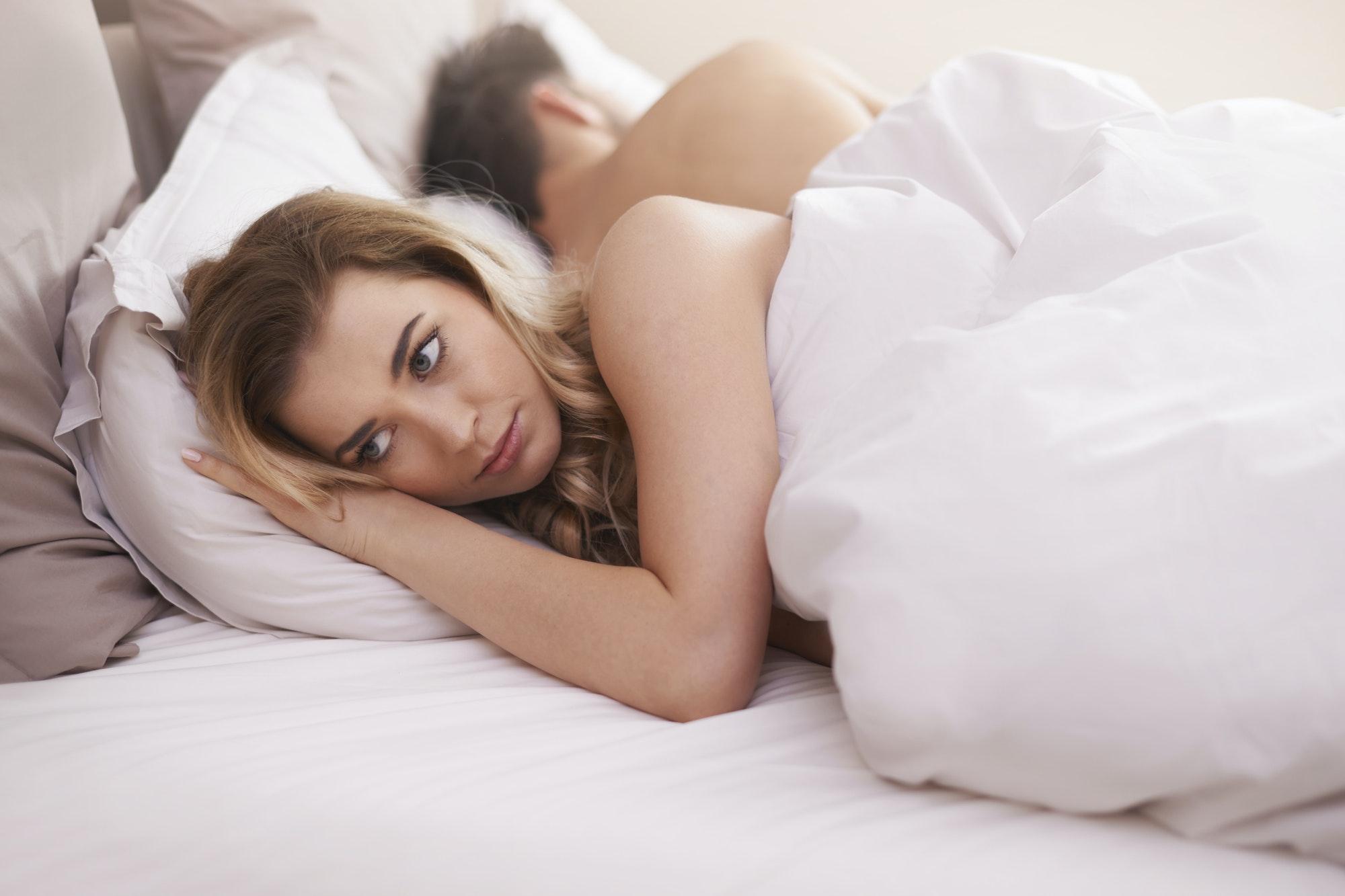 femme triste allongée au lit avec son petit ami. Son couple va mal