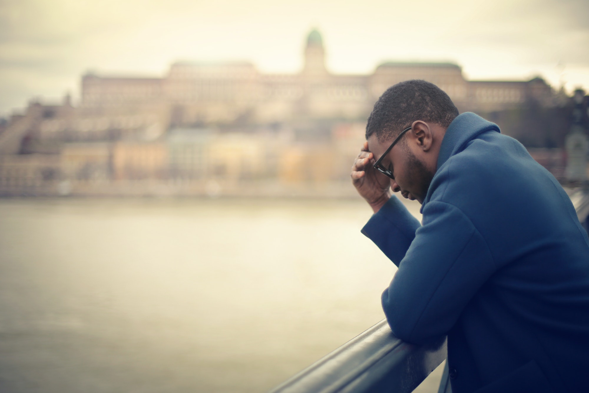 Sad man leaning on bridge