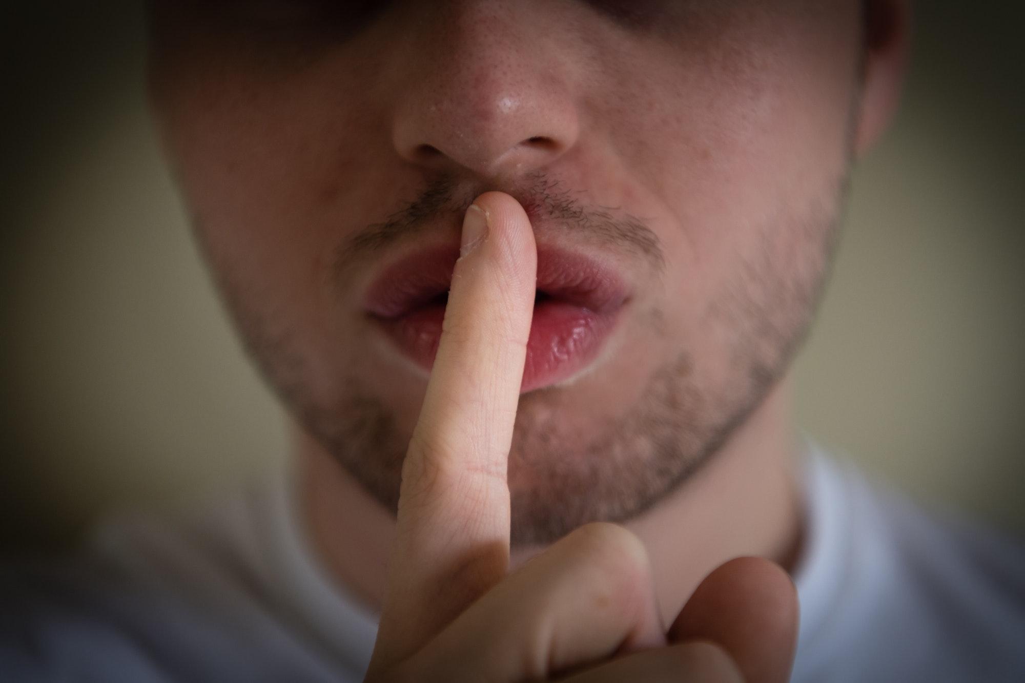 homme fait chut avec son doigt sur la bouche