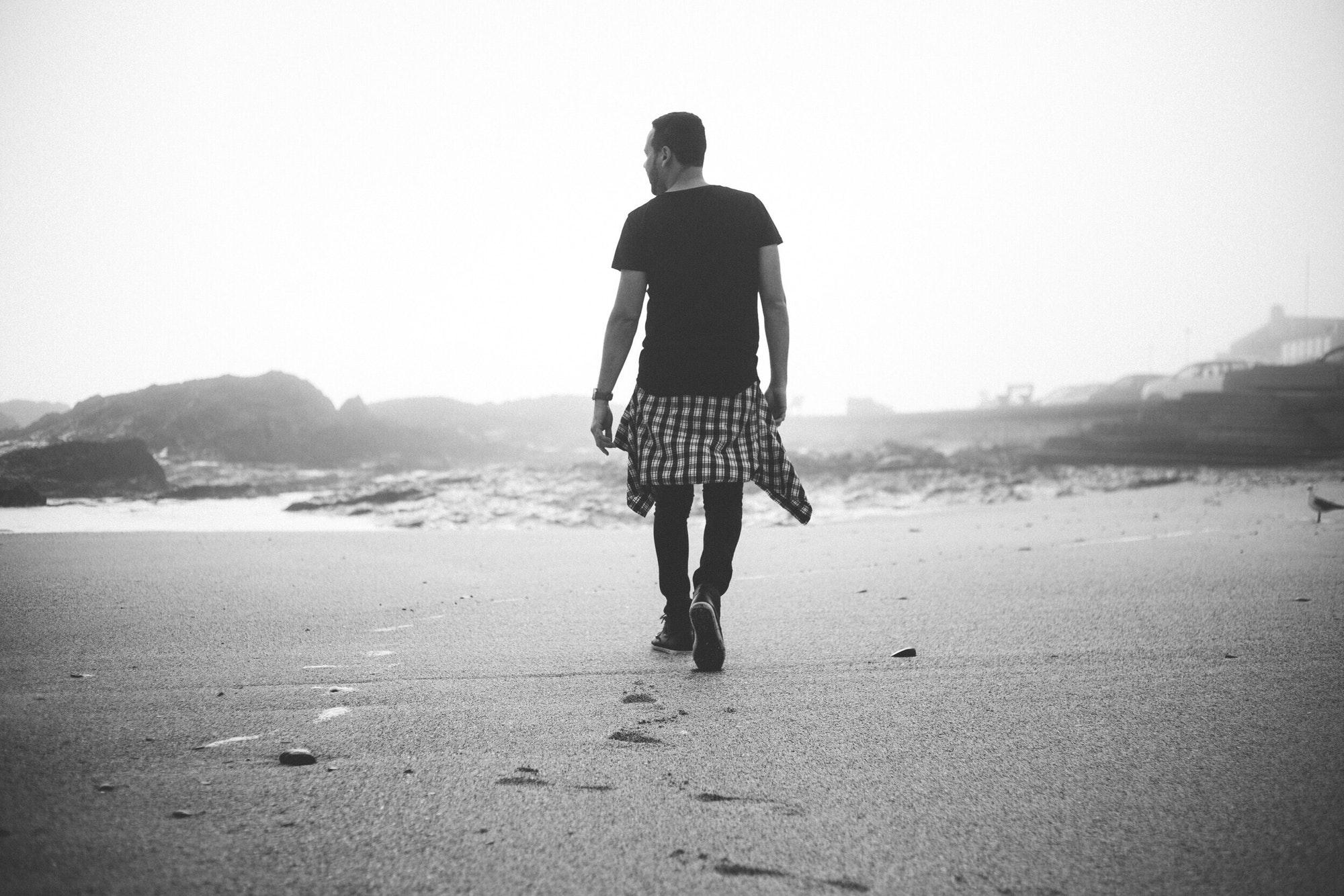vue d'un homme de dos qui marche sur une plage. Photo en noir et blanc